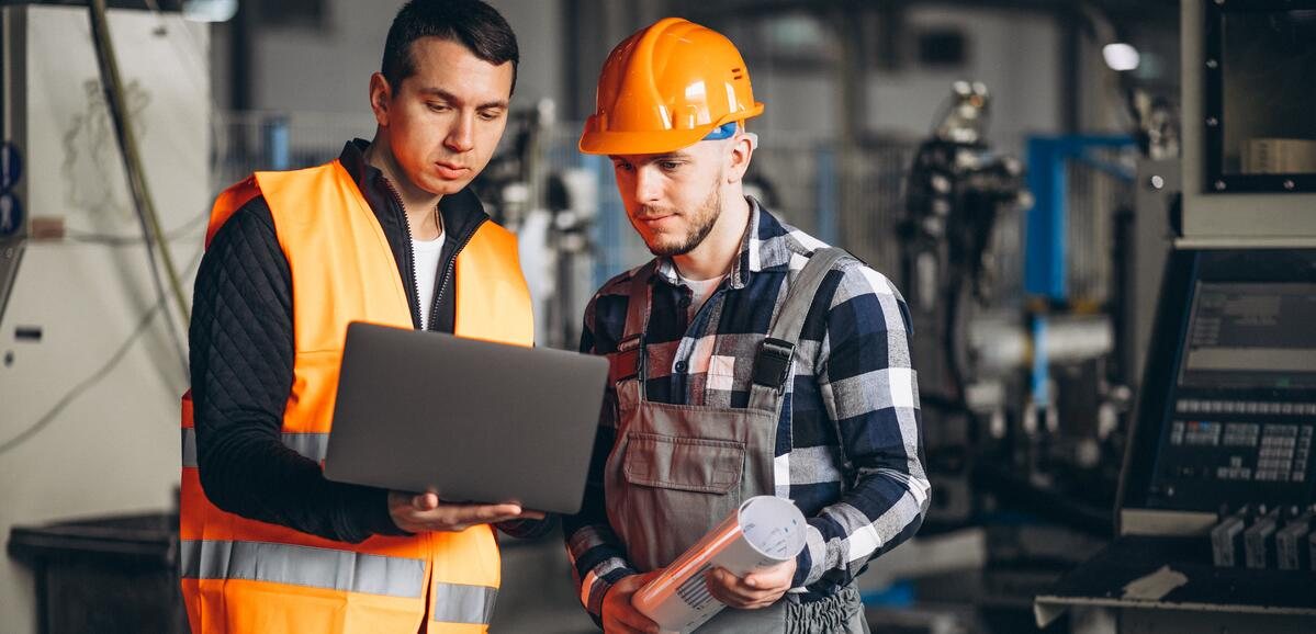 Two men reviewing data at manufacturing site