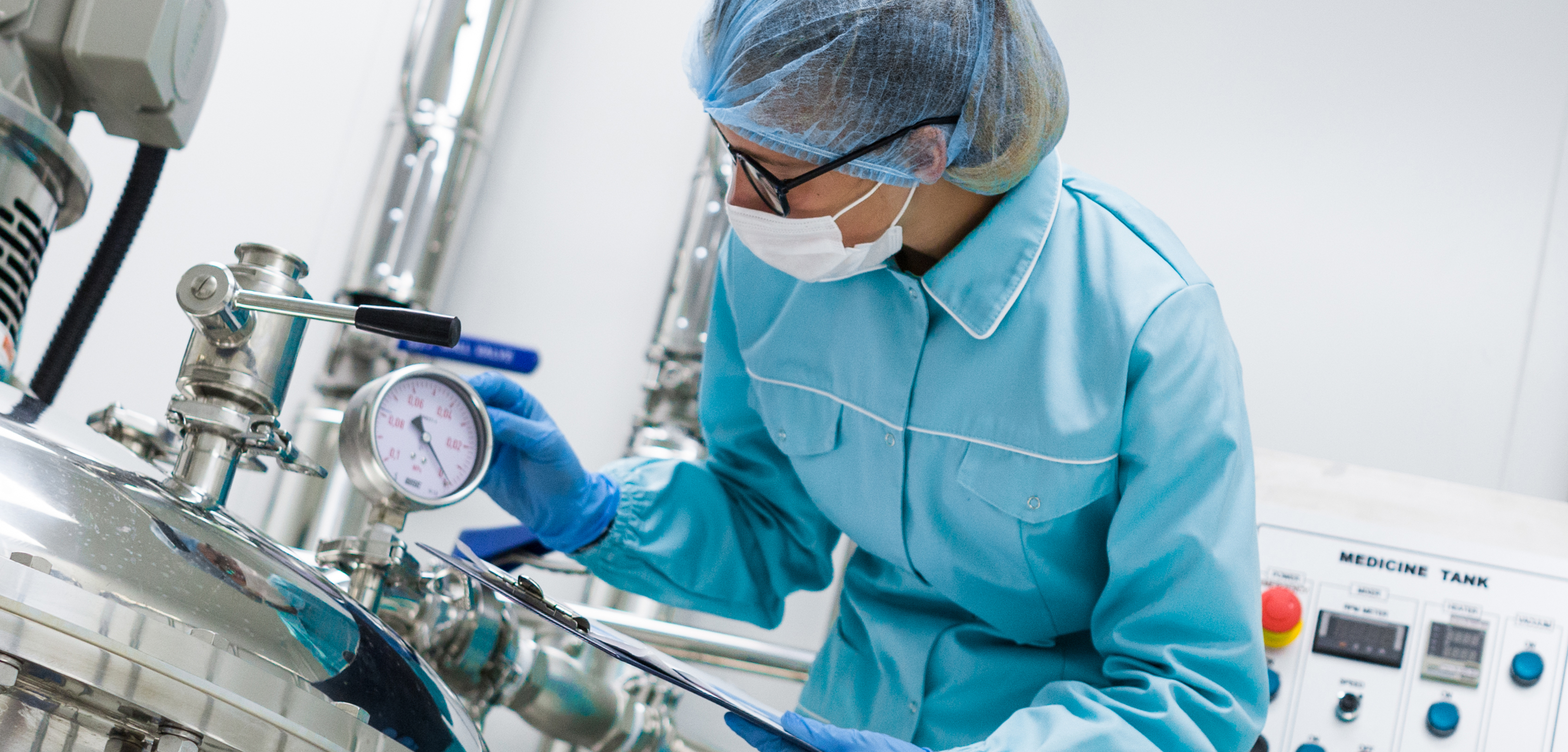 Pharmaceutical worker adjusting temperature controls in lab