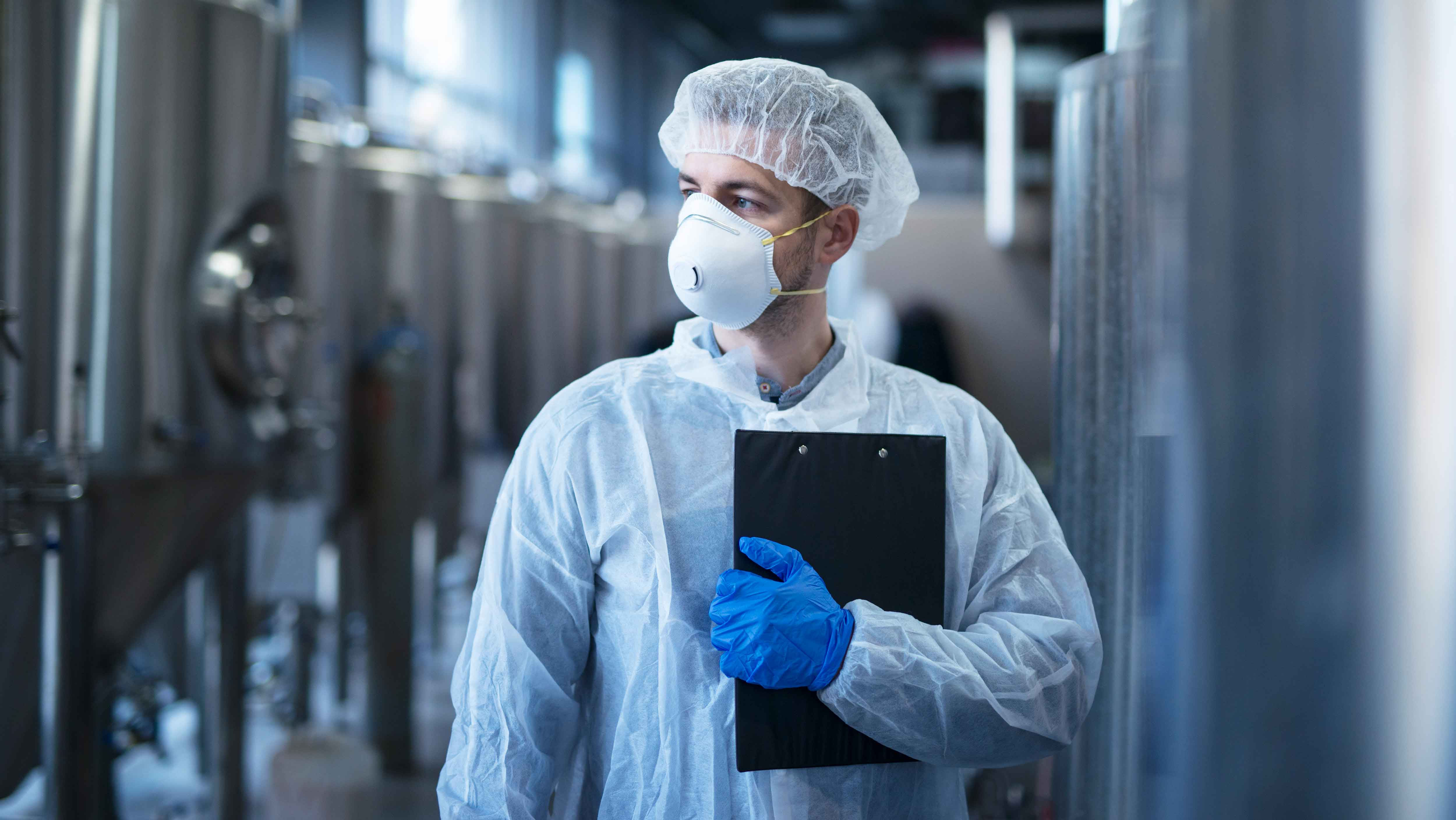 technologist-protective-white-suit-with-hairnet-mask-standing-food-factory