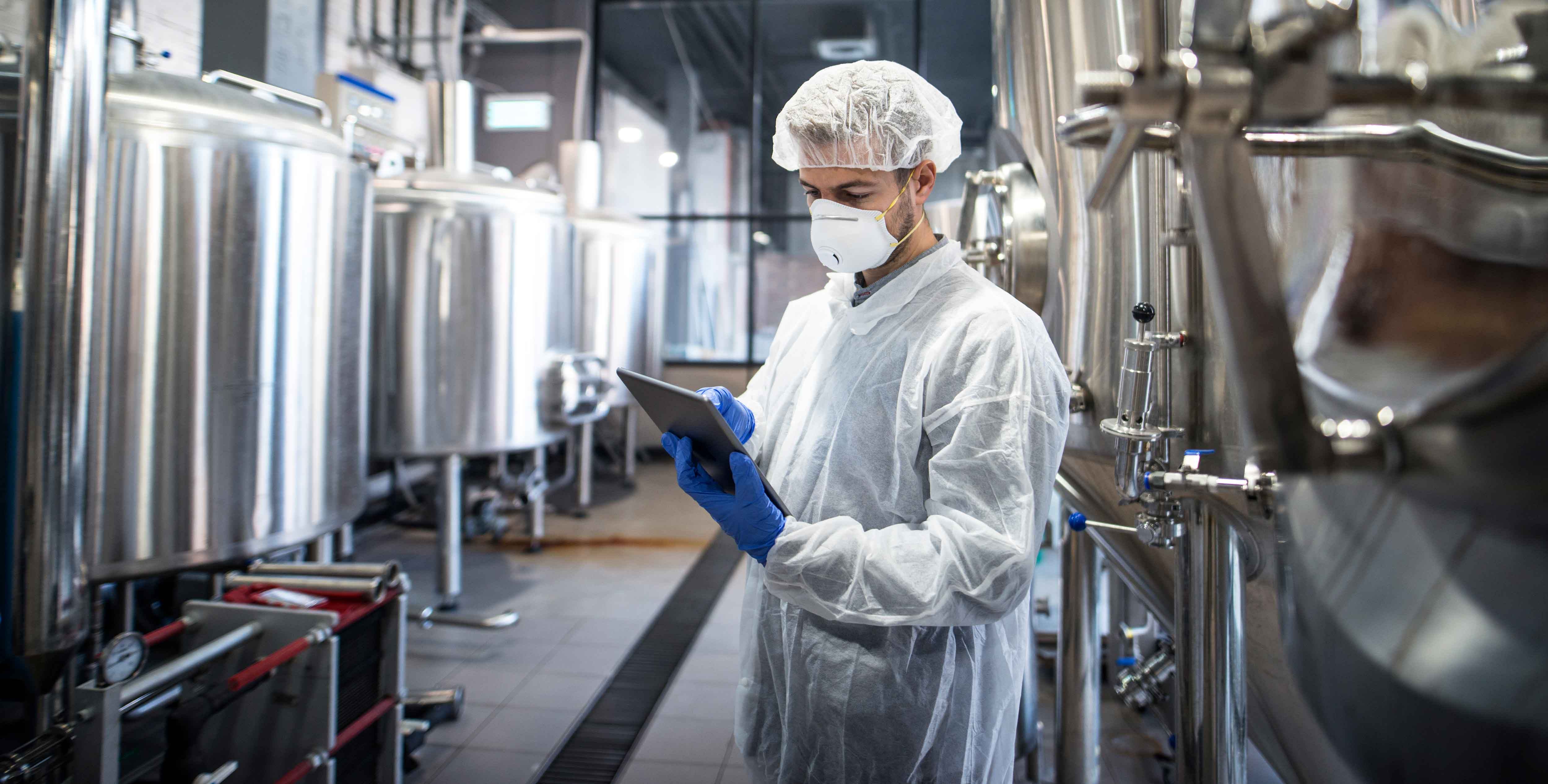 technologist-white-protective-clothes-checking-production-his-tablet