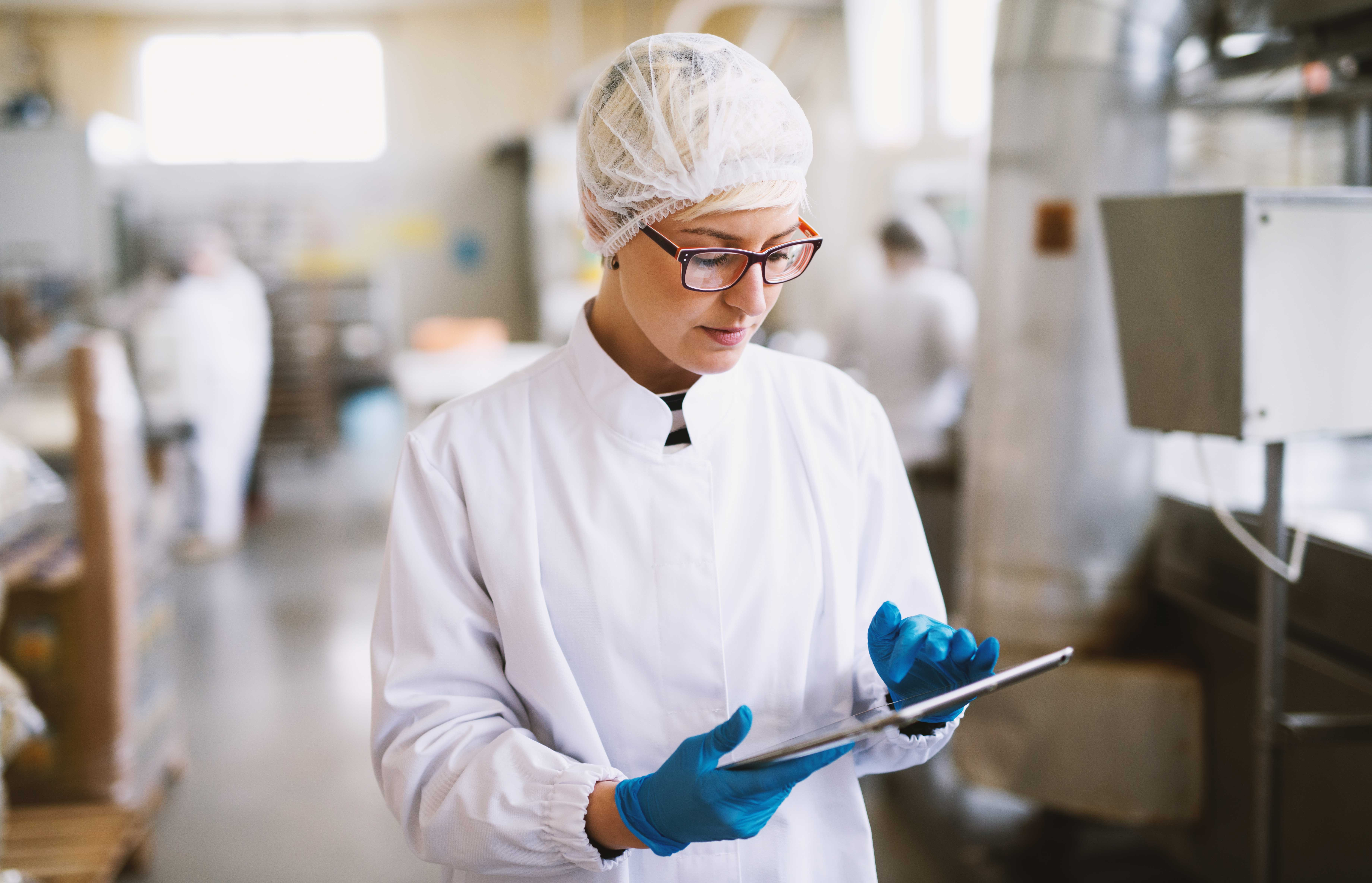 young-focused-female-worker-sterile-clothes-checking-productivity-production-line-food-factory